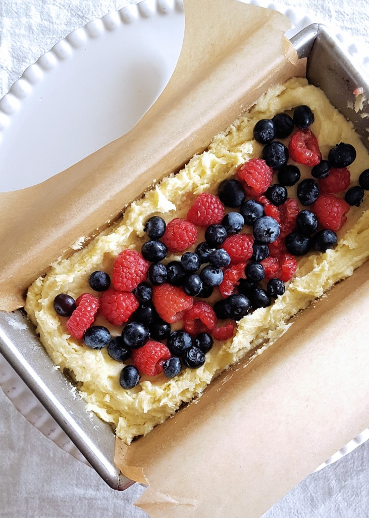 Raw cake batter in a loaf pan, sprinkled with raspberries and blueberries.