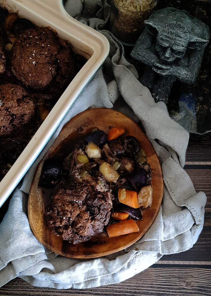 A wooden plate full of colorful root vegetables and a dark dry biscuit.
