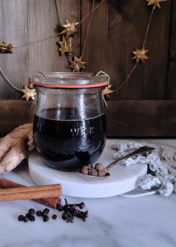 A small jar of dark gingerbread syrup surrounded by whole spices and ginger root.