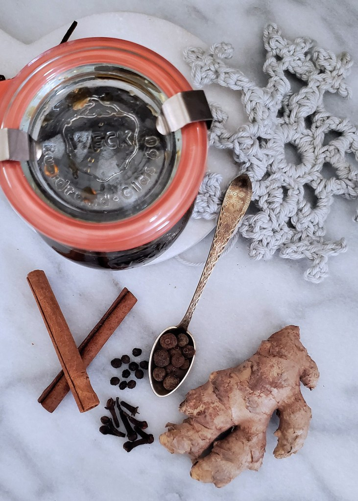 An overhead view of a jar of dark gingerbread syrup with a crocheted snowflake and whole spices.