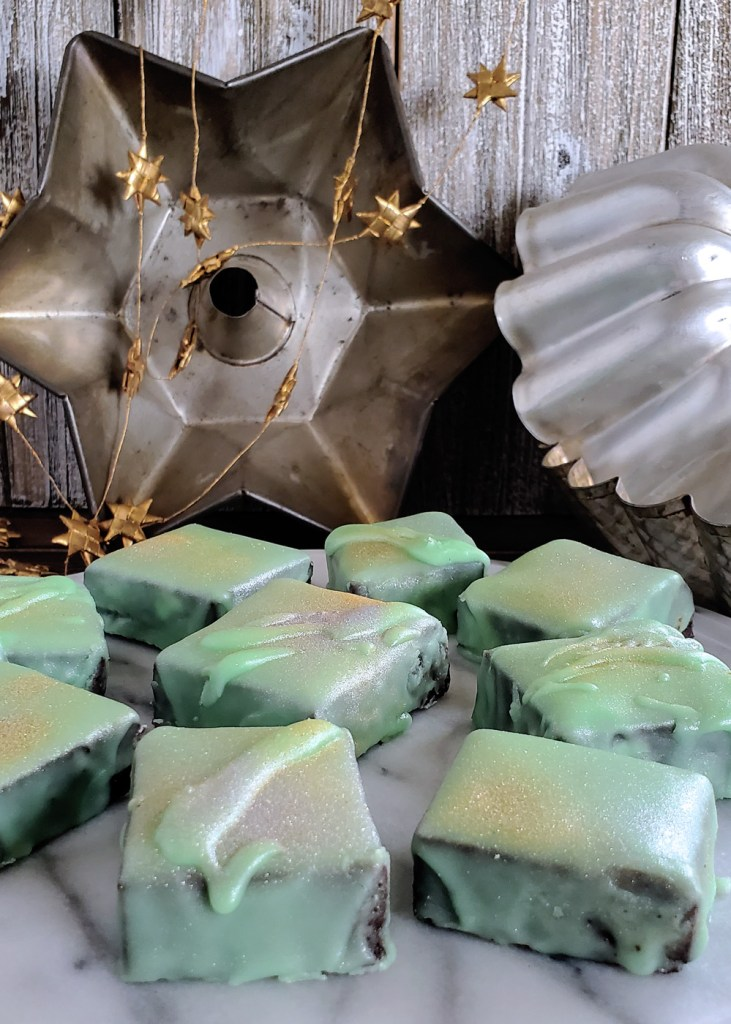 Profile image of mint green brownie bites with star shaped baking pans in the background.