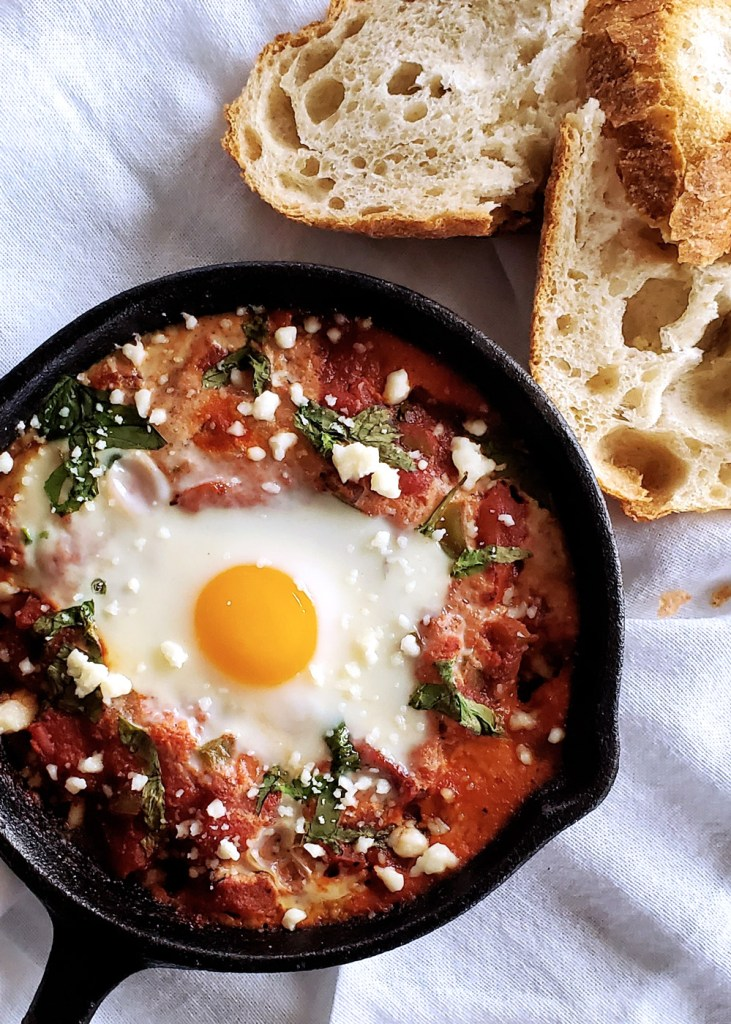 A single baked egg with hunks of fresh bread.