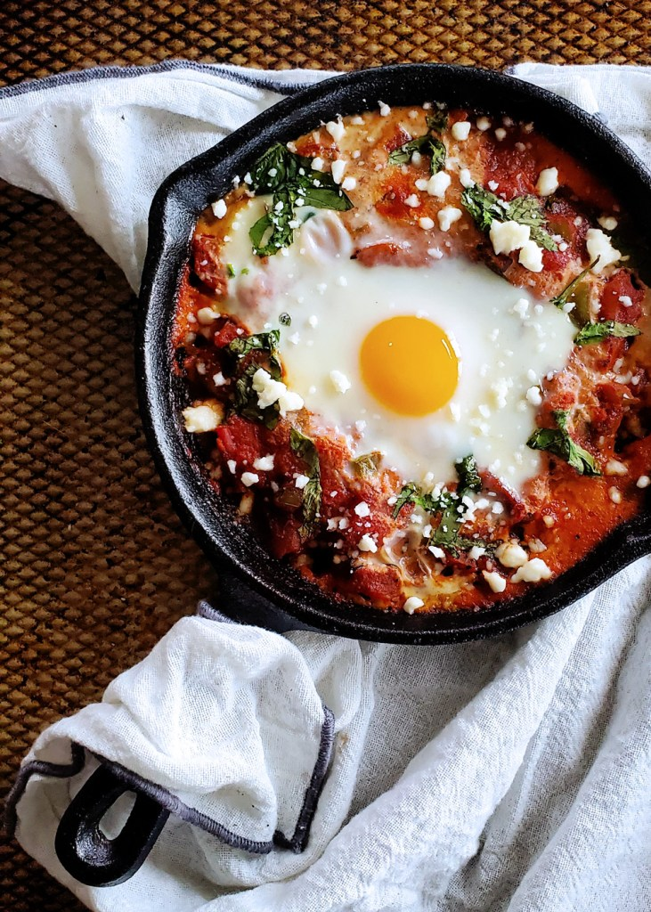 Overview of a single skillet filled with red tomato sauce and topped with a sunny side up egg.