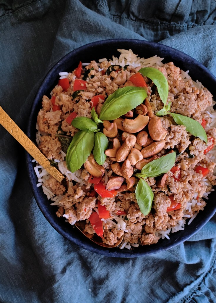 Overhead view of a bowl of cashew basil turkey stir fry topped with green basil leaves.
