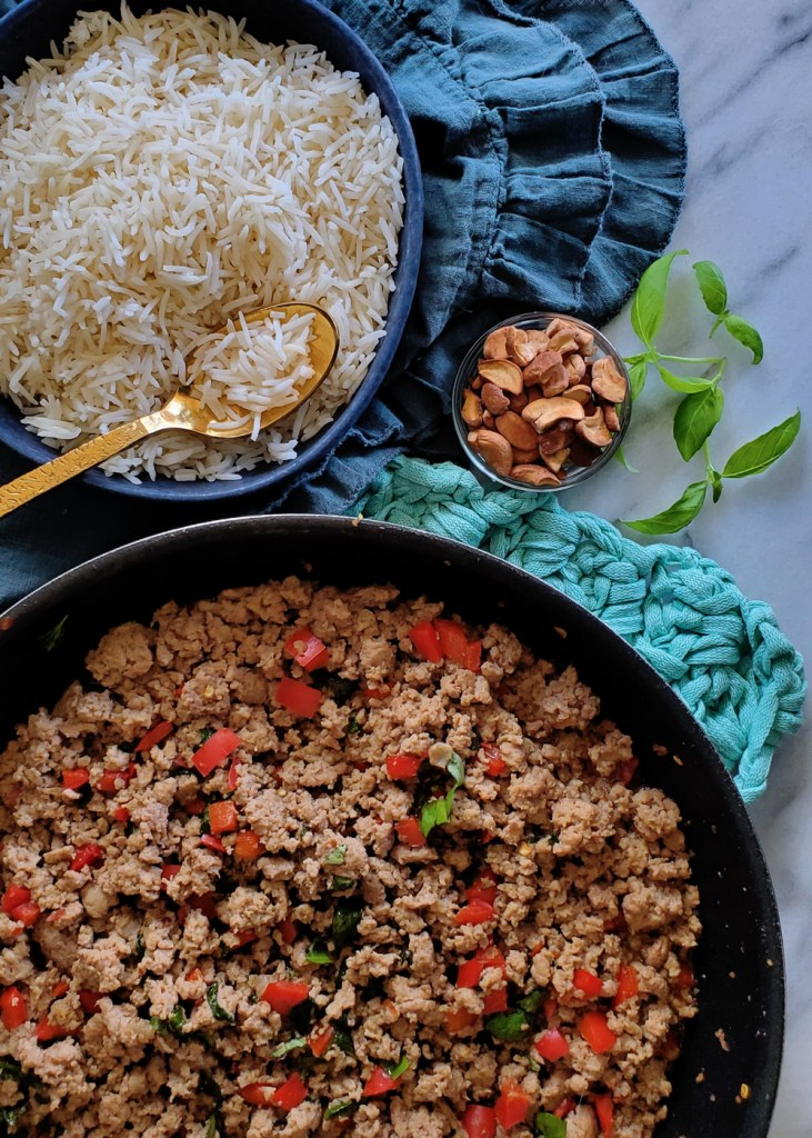 A skillet of basil turkey stir fry with a bowl of rice and a dish of cashews.