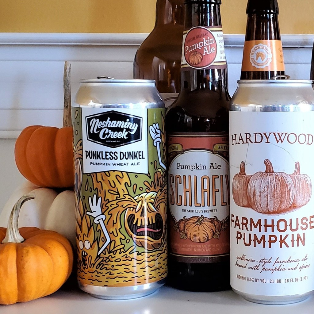 A collection of pumpkin beer cans and bottles with tiny pumpkins.
