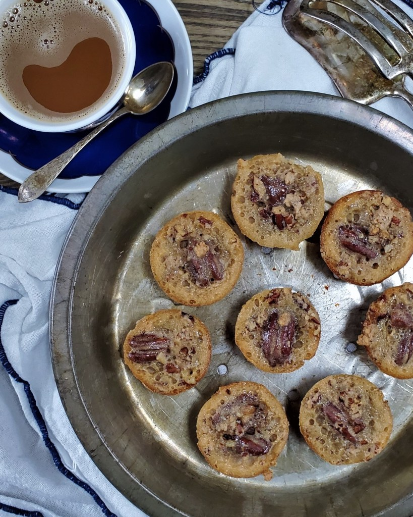 Overhead view of eight pecan pie cookies arranged on a silver pie plate.