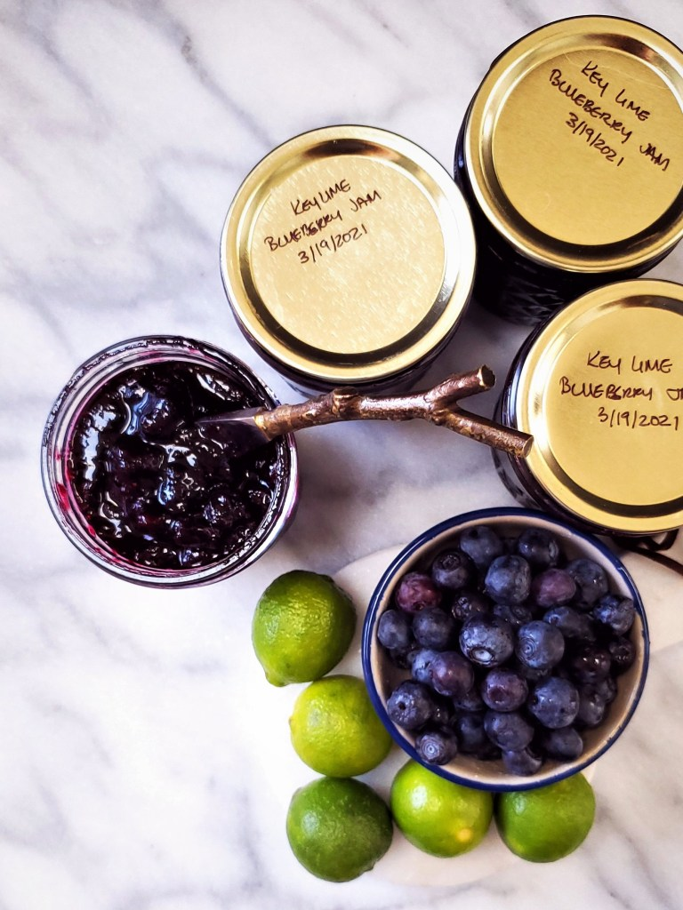Overhead image of three jars of sealed key lime blueberry jam, next to an open jar, a bowl of blueberries, and a pile of key limes.