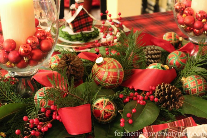 Red and green plaid ornaments, pine cones, faux berries, and red ribbon decorate a table runner of Leland Cypress and Magnolia leaves --Pancakes & Plaid: A Christmas Breakfast Table