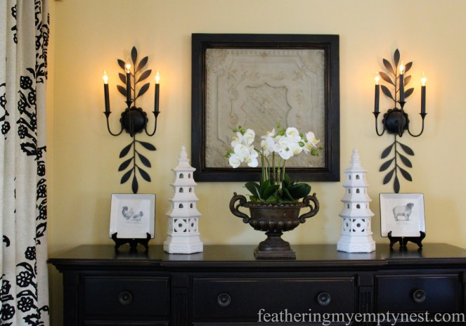 New hard-wired wrought iron sconces flank the freshly chalk-painted and waxed framed Victorian tin ceiling tile --Tips For Using Chalk Paint And Dark Wax