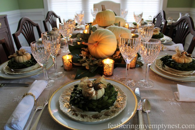 Gold accents and lighted votive candles add a little sparkle to An Nature-Inspired Elegant Thanksgiving Tablescape