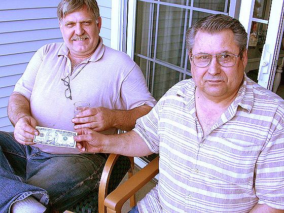 Ronn Lucas handing Ron Reinhold the last $10 for the hook business