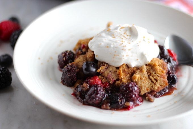 Skillet Berry Cobbler- a rustic, paleo and vegan mixed berry cobbler, topped with whipped coconut almond cream. Perfect for your next family gathering! | fedandfulfilled.com