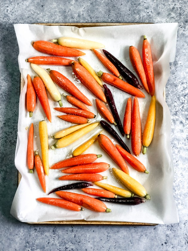 Uncooked rainbow carrots on a baking sheet