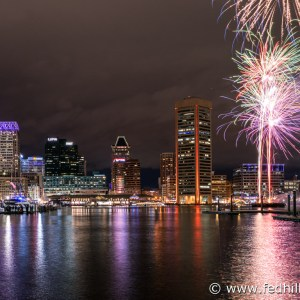 Fine art photograph of New Year's fireworks in sky and reflected in water at night in Inner Harbor, Baltimore City, Maryland.