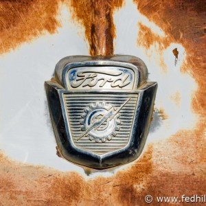 Fine art photo of rusted and decayed antique vintage Ford pickup truck hood ornament.