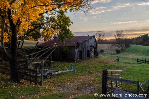 Fine art autumn nature and agriculture photo of sunrise, farmland, barn, trailer.