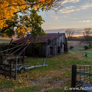 Fine art autumn nature and agriculture photo of sunrise, farmland, barn, trailer.