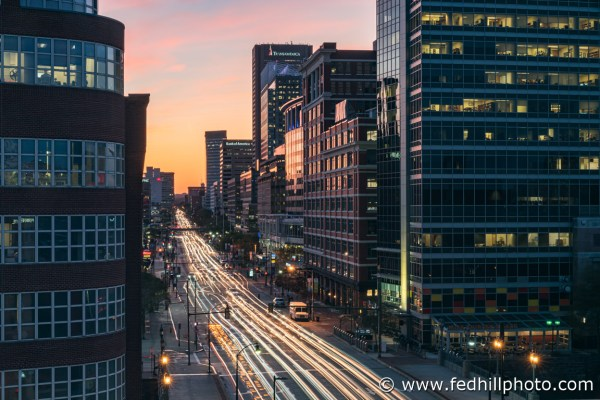 Fine art photo of Pratt St west at sunset in Baltimore City, Maryland. Car headlight streaks. Offices, apartments, condos.