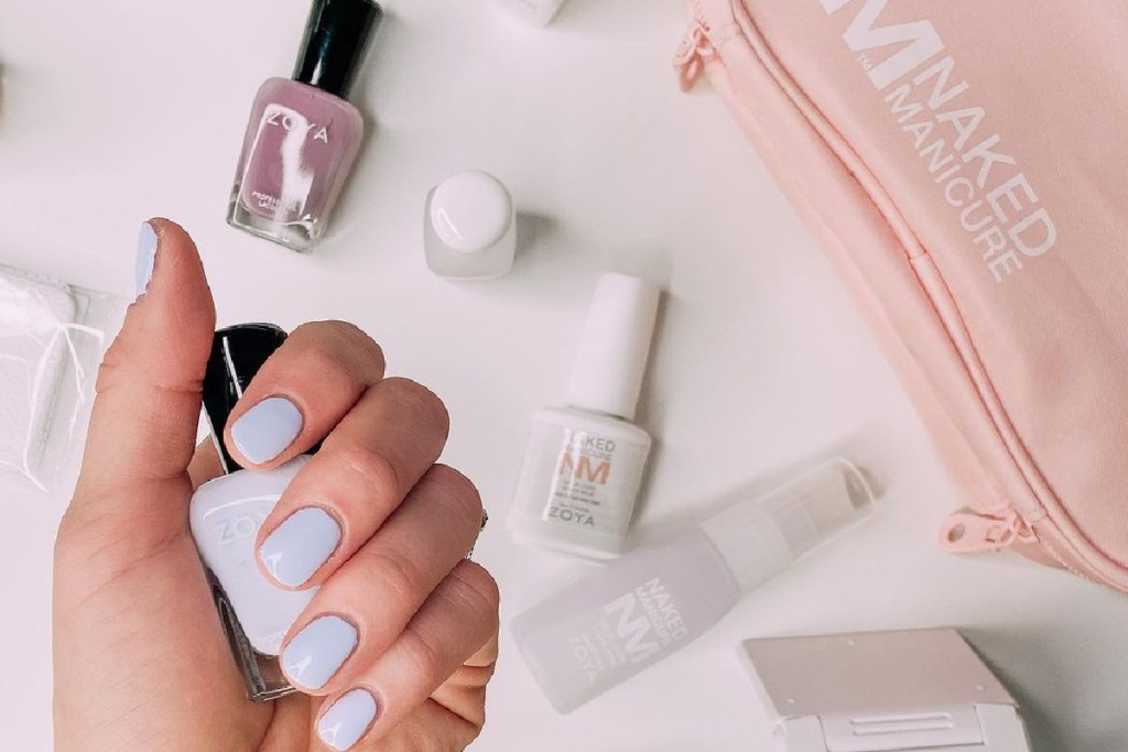 A hand with blue nail polish on the fingernails is holding the Zoya polish bottle over a surface with scattered products from the Gelie-Cure system.