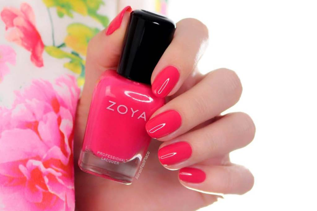 A hand is shown holding a bottle of bright pink ZOYA nail polish, with pink fingernails wrapped around the bottle. The hand is placed next to a flowered shirt.