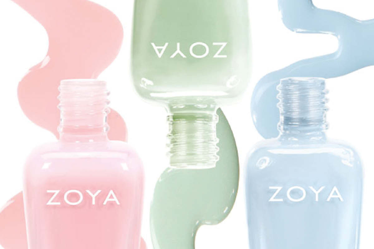 Three pastel ZOYA colors are shown without caps, laying flat on a white surface in alternating directions. Polish spills out of the bottles in curved lines.
