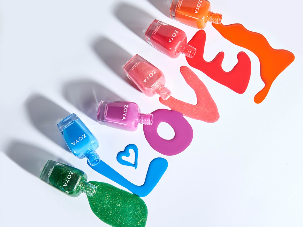 """6 colorful ZOYA nail polishes are laying flat with their colors spilling out to spell the word """"Love"""""""
