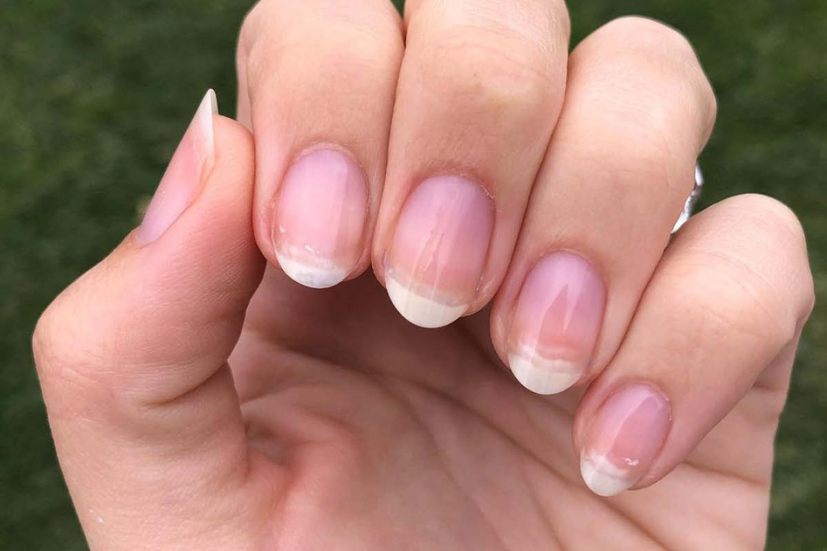 A hand in front of an outdoor, grass background is showing the Gelie-Cure treatment manicure on bare nails.