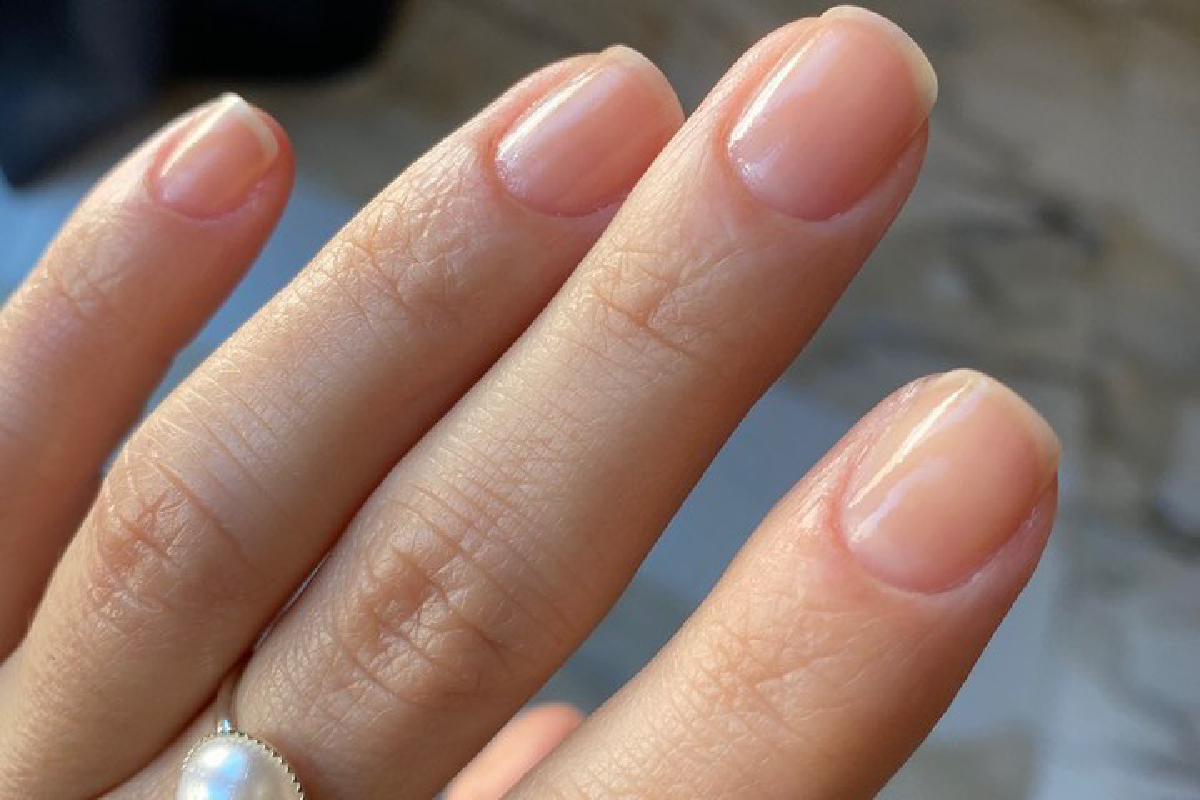 A hand displaying the Rescue Repair treatment on their bare nails.