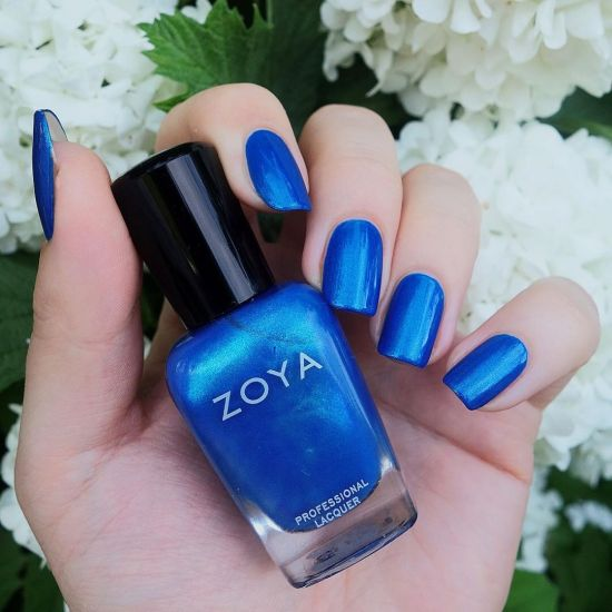 A hand holding a bottle of Tallulah by Zoya while that same color is worn on the fingernails.