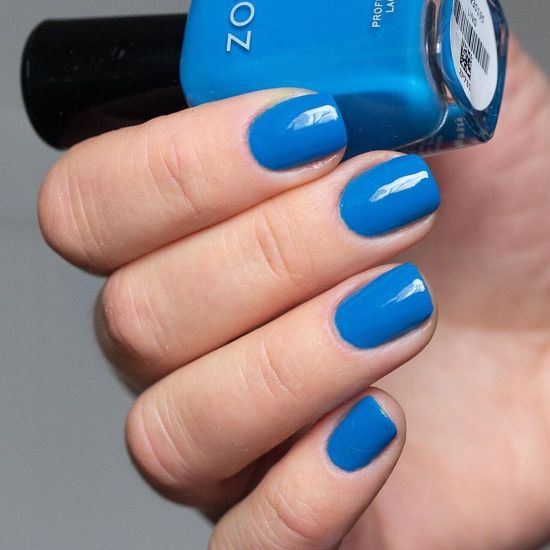 A hand showing Ling by Zoya worn on the fingernails while holding the blue polish bottle.