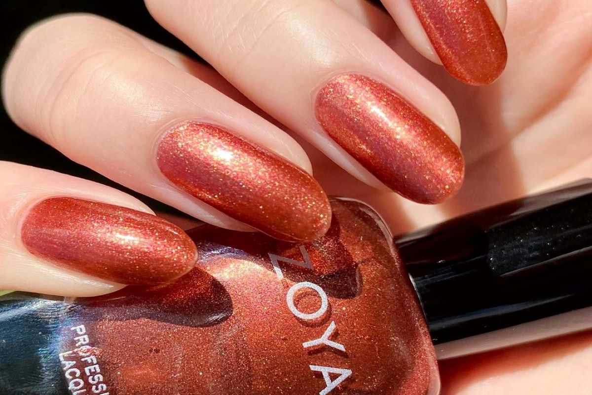 @Need_more_fingers wearing ZOYA Autumn on her nails and holding the bottle.