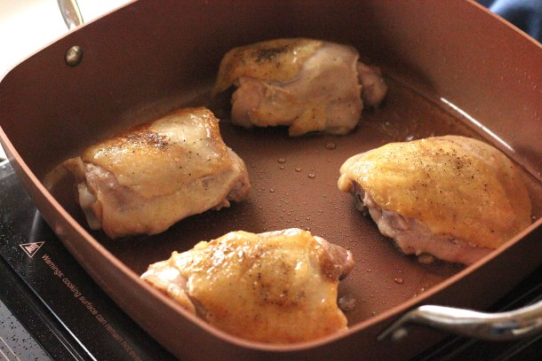 Browned chicken thighs in a copper pan