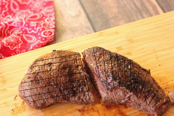 Image of tri tip on a cutting board with lines to show cutting directions