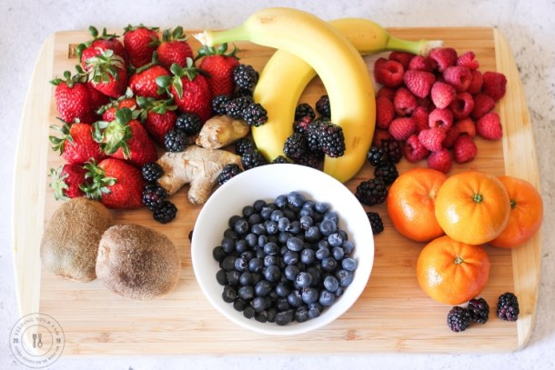 berries, bananas, oranges and kiwi on a cutting board
