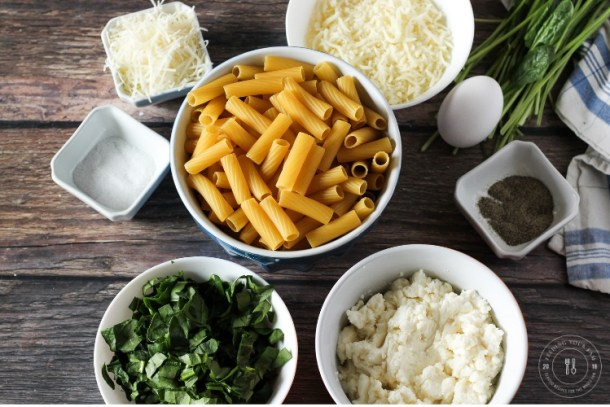 ingredients for spinach ricotta pasta. Rigatoni noodles, spinach, ricotta, mozzarella, parmesan, salt and pepper