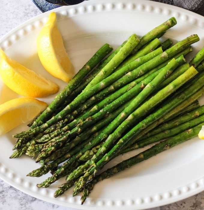 grilled asparagus on a white plate with lemon wedges
