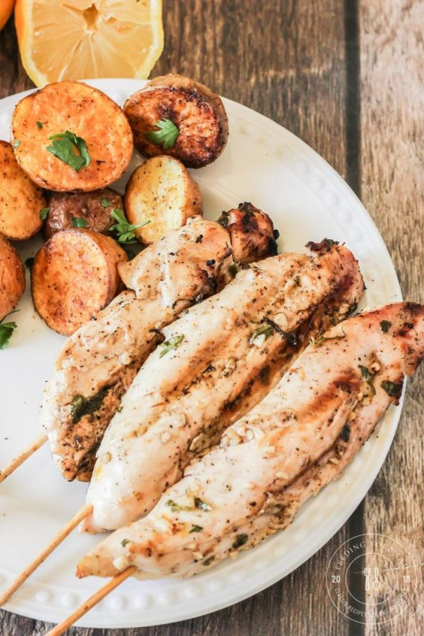 chicken kabobs on a white plate with potatoes