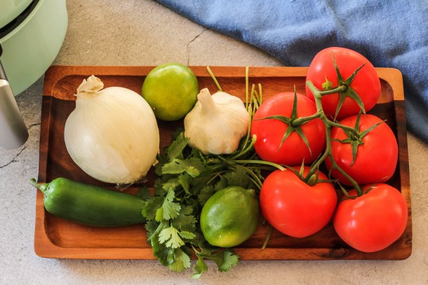 tomatoes, onion, garlic, limes, cilantro and jalapeno on a wooden platter