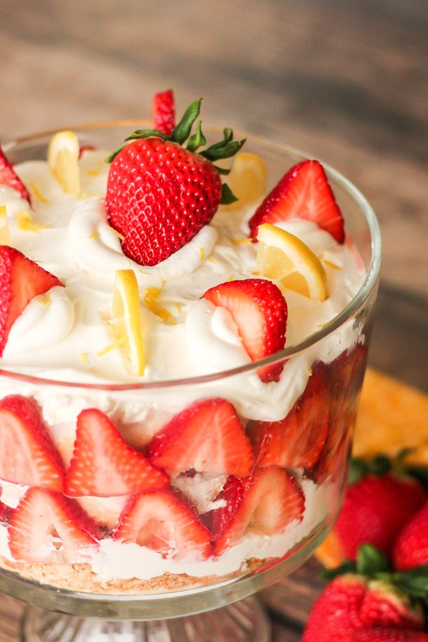 strawberry trifle with strawberries and lemon wedges on top
