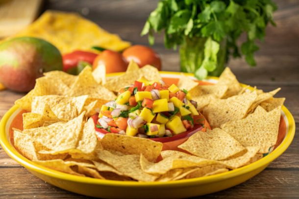 mango salsa on a platter with chips