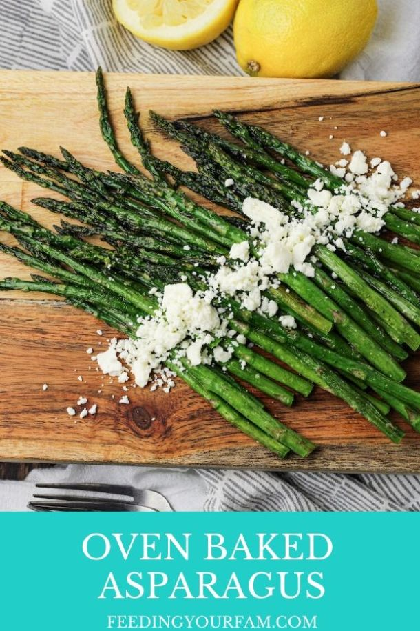 asparagus on a wooden platter sprinkled with feta cheese
