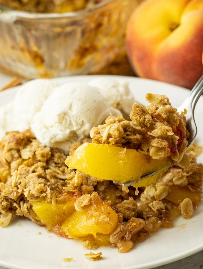 fork lifting a scoop of peach crisp off a white plate