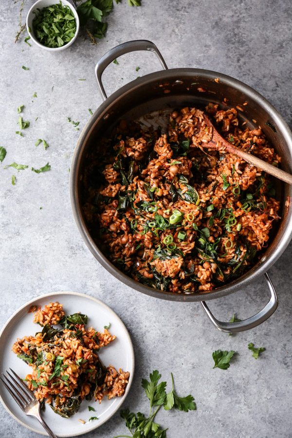 vegan jambalaya with greens in a pot with a plate