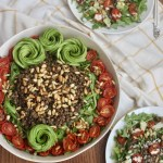 vegan arugula lentil salad with cumin toasted pine nuts, oven roasted tomatoes, and avocados