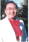 Smiling woman with glasses wearing a white suit with a red shirt