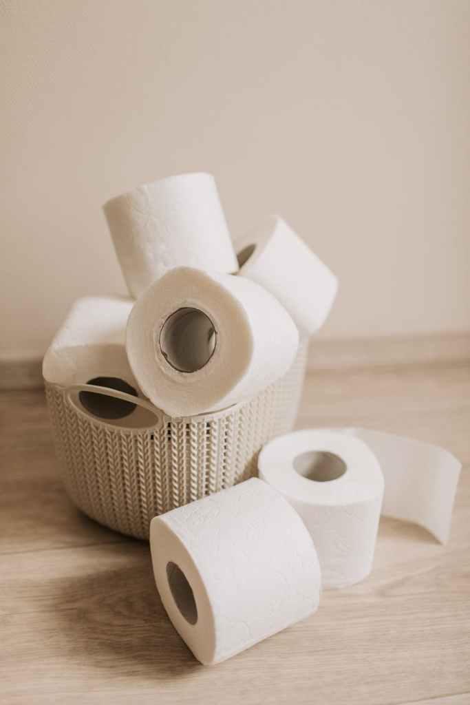 tubes of white toilet paper and plastic basket on bathroom floor