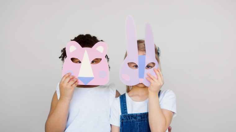 two kids covering their faces with a cutout animal mask