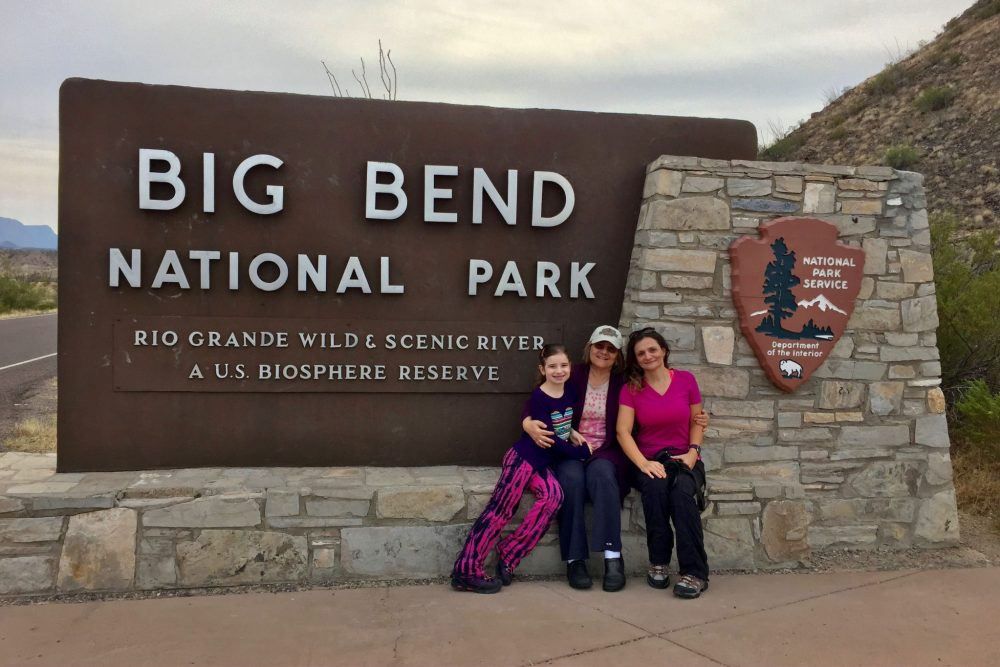 In front of Big Bend National Park sign, one of two national parks in Texas