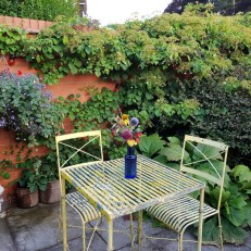 Photo of a yellow iron table and two chairs in Clare's garden